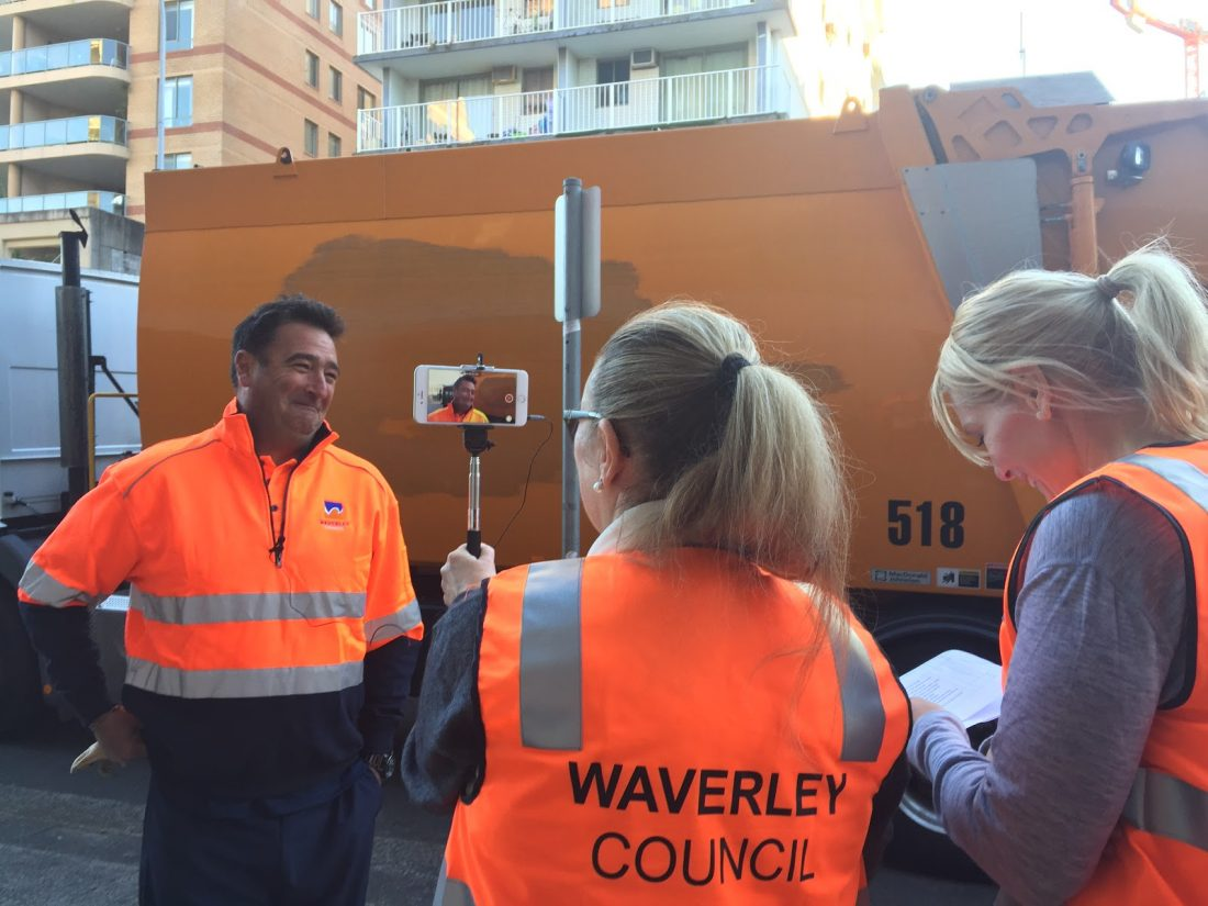 Two staff members from Waverley Council, holding a smartphone and interviewing a garbage man.